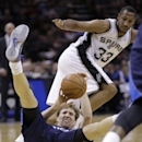 Dallas Mavericks' Dirk Nowitzki, bottom, of Germany, falls to the floor as he and San Antonio Spurs' Boris Diaw (33), of France, chase a loose ball during the first half of Game 2 of the opening-round NBA basketball playoff series on Wednesday, April 23,