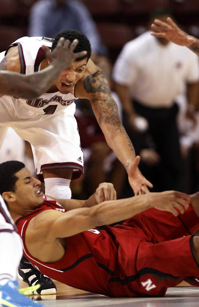 Nebraska's Tai Webster, bottom, passes the ball against the pressure from Massachusetts' Chaz Williams, left, and Maxie Esho, rear, in the second half at the Charleston Classic NCAA college basketball tournament in Charleston, S.C., Thursday, Nov. 21, 2013