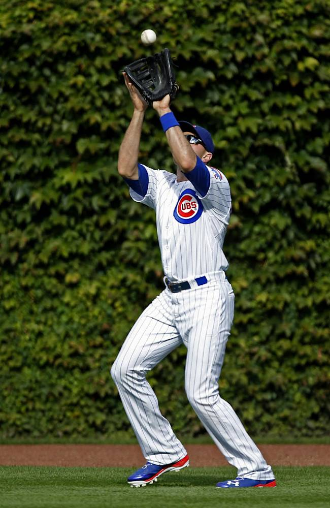 Chicago Cubs right fielder Nate Schierholtz catches a fly ball hit by the Atlanta Braves' Andrelton Simmons during the third inning of a baseball game on Saturday, Sept. 21, 2013, in Chicago