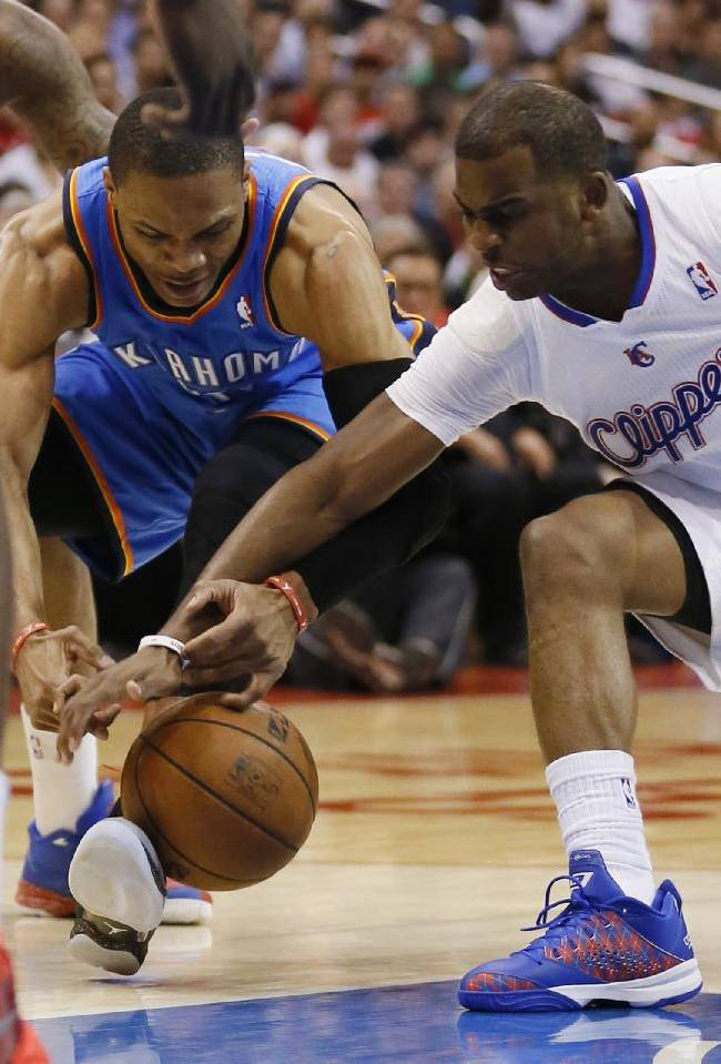 Oklahoma City Thunder guard Russell Westbrook, left, and Los Angeles Clippers guard Chris Paul reach for a loose ball during the first half of an NBA basketball game in Los Angeles, Wednesday, April 9, 2014