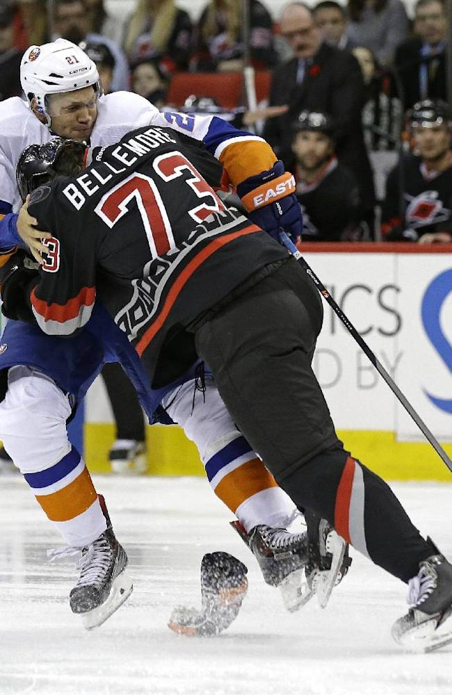 Carolina Hurricanes' Brett Bellemore (73) checks New York Islanders' Kyle Okposo (21) during the first period of an NHL hockey game in Raleigh, N.C., Thursday, Nov. 7, 2013
