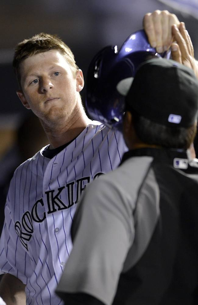 Colorado Rockies' DJ LeMahieu celebrates with teammates in the dugout after scoring on a Charlie Blackmon RBI-single against the Philadelphia Phillies during the seventh inning of a baseball game on Friday, April 18, 2014, in Denver