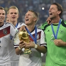Germany's Bastian Schweinsteiger celebrates with the trophy after the World Cup final soccer match between Germany and Argentina at the Maracana Stadium in Rio de Janeiro, Brazil, Sunday, July 13, 2014. Germany won the match 1-0