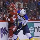 St. Louis Blues defenseman Carl Gunnarsson (4) hits Arizona Coyotes right wing David Moss (18) into the boards as they try for the puck during the first period of an NHL hockey game Tuesday, Jan. 6, 2015, in Glendale, Ariz The Associated Press