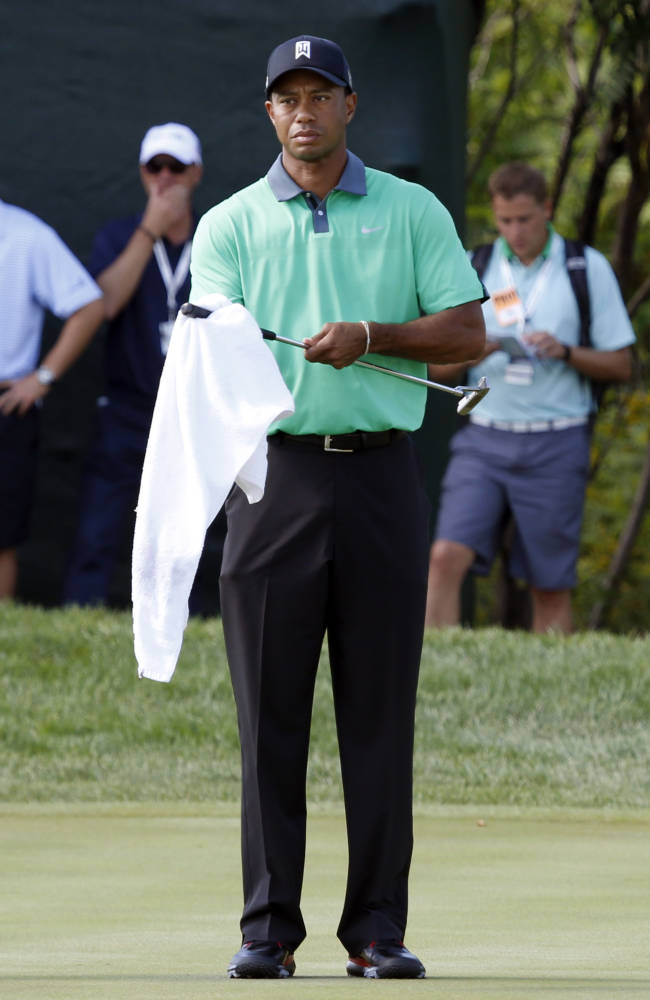Tiger Woods wipes off his club during the first round of the BMW Championship golf tournament at Conway Farms Golf Club in Lake Forest. Ill., Thursday, Sept. 12, 2013