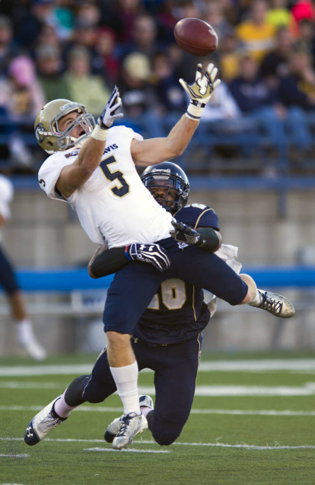 In this photo provided by Montana State University, Montana State safety James Nelson (26) disrupts a reception by UC Davis wide receiver Tom Hemminsen (5) during the second half of an NCAA college football game on Saturday, Oct. 26, 2013, in Bozeman, Mont. MSU won 34-17