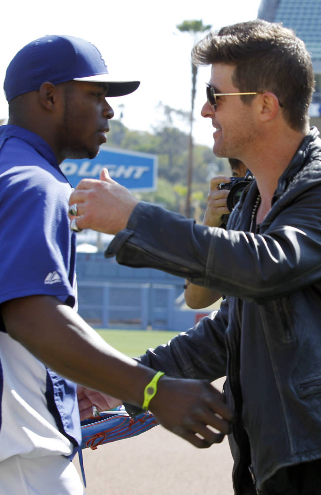 Los Angeles Dodgers' Yasiel Puig, left, meets musician Robin Thicke, who will sing in a concert prior to a baseball game against the San Francisco Giants on Saturday, April 5, 2014, in Los Angeles. (AP Photo/Alex Gallardo)