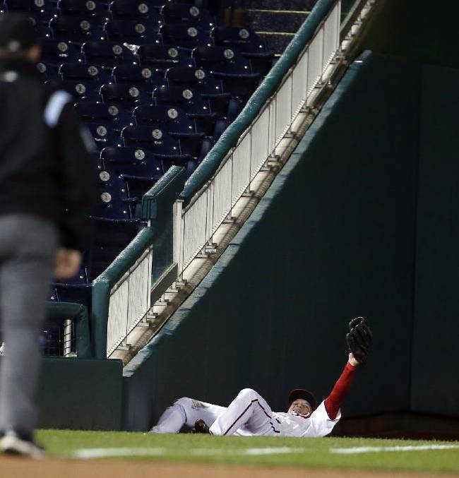 Washington Nationals left fielder Nate McLouth holds his foul ball catch, hit by Los Angeles Dodgers' Dee Gordon, for an out during the eighth inning of a baseball game at Nationals Park, Tuesday, May 6, 2014, in Washington. McLouth was injured on the play and left the game. The Nationals won 4-0