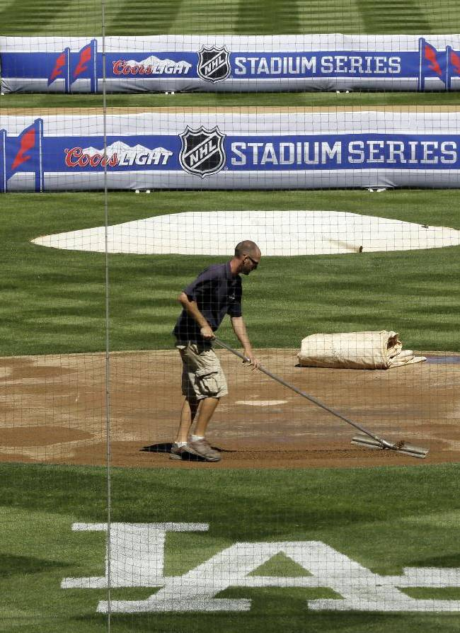Dodger Stadium goundskeepers add sand around home plate before an NHL hockey news conference Thursday, Sept. 26, 2013, in Los Angeles, announcing the outdoor hockey game between the Los Angeles Kings and Anaheim Ducks. The game will be played on a temporary rink on the baseball field on Jan. 25, 2014