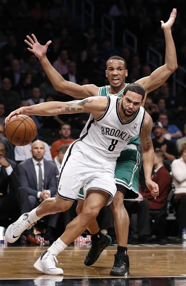 Brooklyn Nets guard Deron Williams (8) drives around Boston Celtics guard Avery Bradley (0) in the first half of their their NBA basketball game, Tuesday, Dec. 10, 2013, in New York. Williams scored 25 points for the Nets as they defeated the Celtics 104-96. Bradley led with Celtics with 22 points