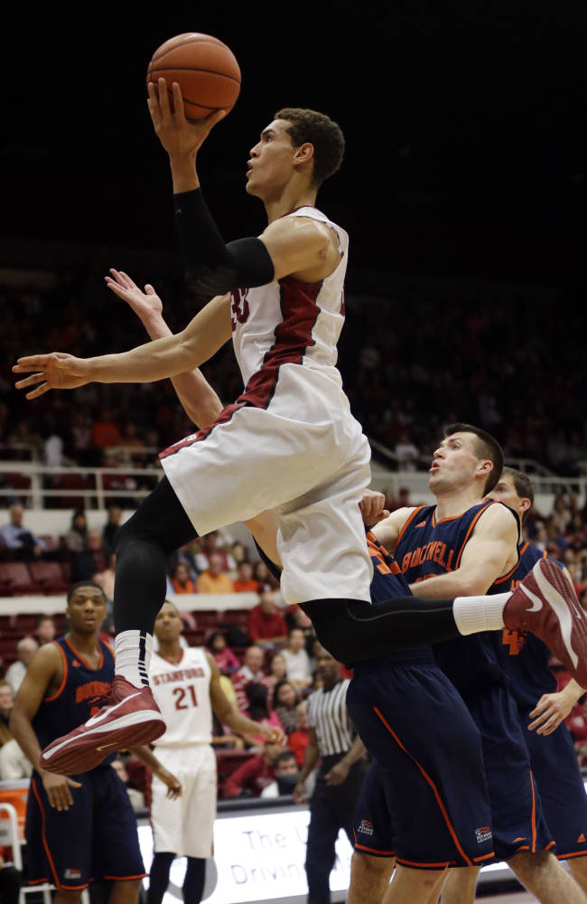 Stanford's Dwight Powell, top, drives to the basket past Bucknell's Brian Fitzpatrick, right, during the first half of an NCAA college basketball game Friday, Nov. 8, 2013, in Stanford, Calif