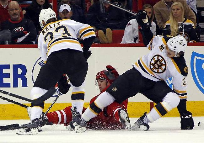 Carolina Hurricanes' Chris Terry, center, battles with Boston Bruins' Chris Kelly (23) and Loui Eriksson (21) during the first period of an NHL hockey game in Raleigh, N.C., Monday, Nov. 18, 2013