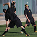Pittsburgh Pirates pitchers Mark Melancon, foreground, and Jason Grilli, right, warm up before taking part in an informal workout at Pirates City in Bradenton, Fla., Wednesday, Feb. 12. The first official day of baseball spring training for Pirates pitch