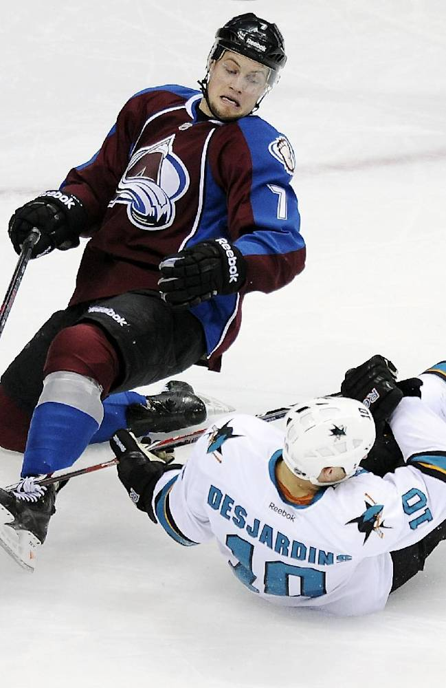 Colorado Avalanche center John Mitchell, left, and San Jose Sharks center Andrew Desjardins, right, fall to the ice in the first period of an NHL hockey game on Saturday, Jan. 4, 2014, in Denver