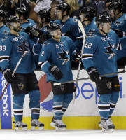 San Jose Sharks' Joe Pavelski (8) celebrates his goal with teammates on the bench during the second period of an NHL hockey game against the Toronto Maple Leafs on Tuesday, March 11, 2014, in San Jose, Calif. (AP Photo/Marcio Jose Sanchez)