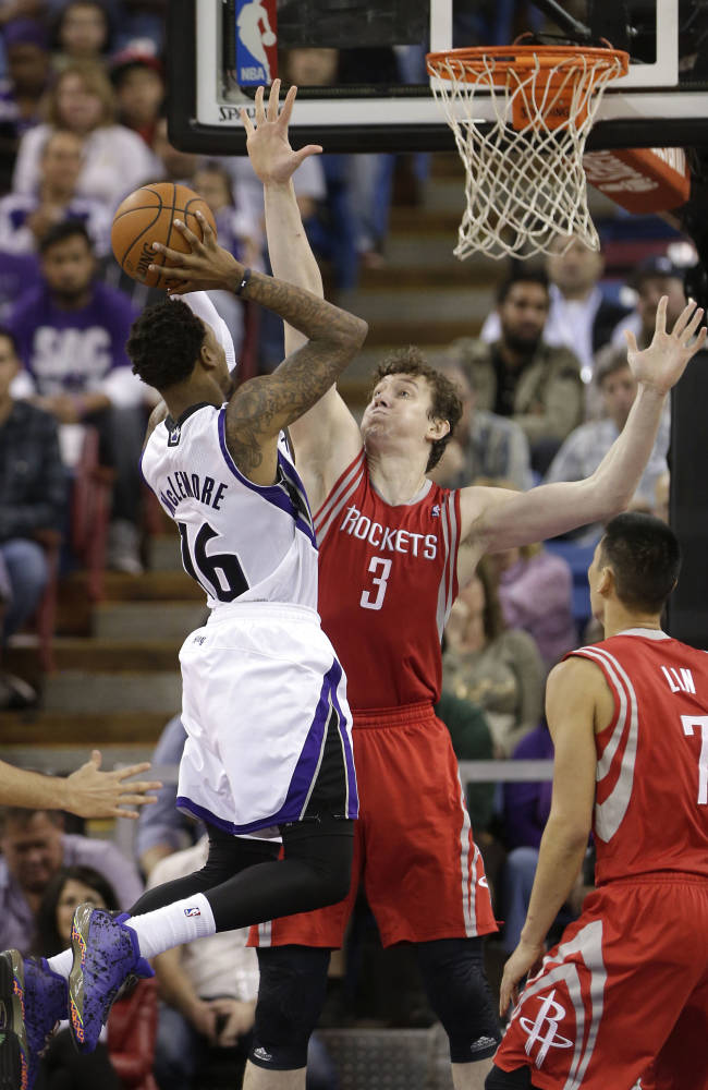Sacramento Kings guard Ben McLemore, left, goes the basket against Houston Rockets Omer Asik, of Turkey, center, during the  fourth quarter of an NBA basketball game in Sacramento, Calif., Tuesday Feb. 25, 2014.  The Rockets won 129-103