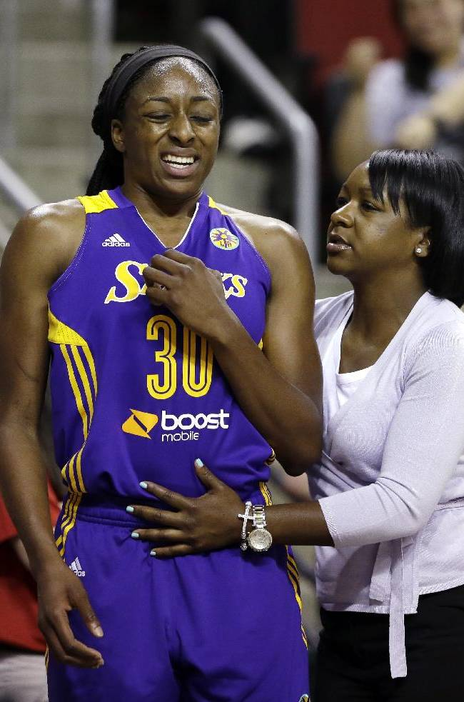 Los Angeles Sparks' Nneka Ogwumike, left, is tended to by a trainer after coming out of the basketball game against the Seattle Storm in the first half Friday, May 16, 2014, in Seattle. The Sparks won 80-69