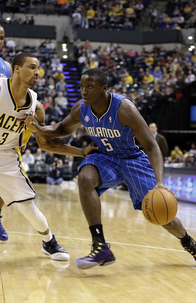 Orlando Magic guard Victor Oladipo, right, drives on Indiana Pacers guard George Hill in the first half of an NBA basketball game in Indianapolis, Monday, Feb. 3, 2014