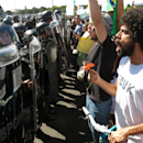 Demonstrators protest in front of the National Stadium before the opening soccer match of the Confederations Cup between Brazil and Japan, in Brasilia, Brazil, Saturday, June 15, 2013. Police say about 1,000 people in the Brazilian capital have protested against the Confederations Cup claiming the money spent to host the tournament would be better spent elsewhere. (AP Photo/Tales Azzoni)