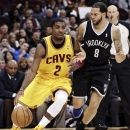 Cleveland Cavaliers' Kyrie Irving (2) tries to get past Brooklyn Nets' Deron Williams (8) during the second quarter of an NBA basketball game, Wednesday, April 3, 2013, in Cleveland. The Nets won 113-95. (AP Photo/Tony Dejak)
