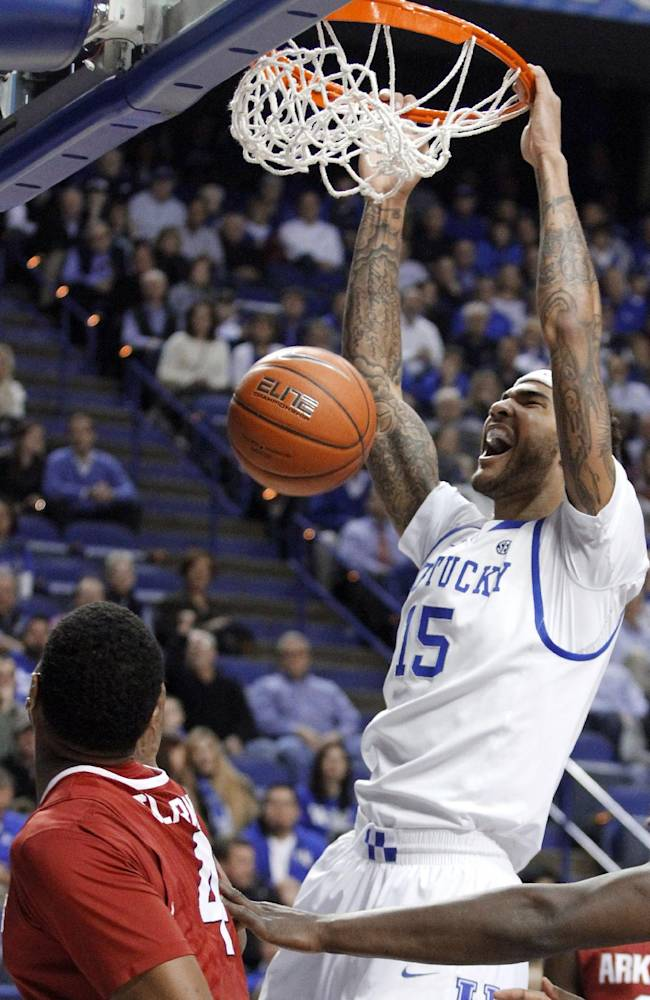 Kentucky's Willie Cauley-Stein (15) dunks next to Arkansas' Coty Clarke (4) during the first half of an NCAA college basketball game Thursday, Feb. 27, 2014, in Lexington, Ky