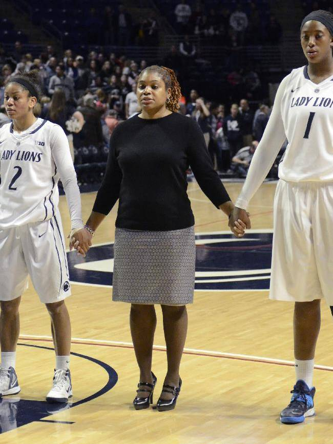 Penn State head coach Coquese Washington, center, joins hands with her team for the singing of Penn State's Alma Mater after the team's loss to Connecticut in an NCAA college basketball game Sunday, Nov. 17, 2013, in State College, Pa