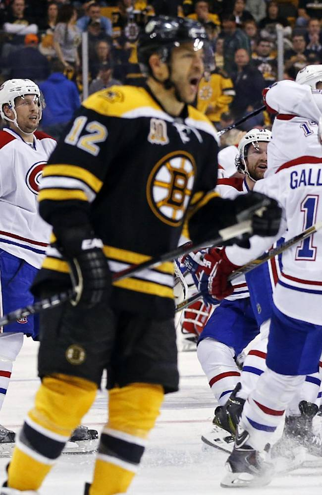 Montreal Canadiens teammates jump on P.K. Subban, right, after his game-winning goal in the second overtime period as Boston Bruins right wing Jarome Iginla (12) skates away in Game 1 of an NHL hockey second-round playoff series in Boston, Thursday, May 1, 2014