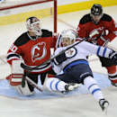 Winnipeg Jets' Devin Setoguchi goes down after getting hit with the puck in front of New Jersey Devils goaltender Martin Brodeur (30) and Marek Zidlicky (2) during the third period of an NHL hockey game Monday, Nov. 25, 2013, in Newark, N.J. The Jets def