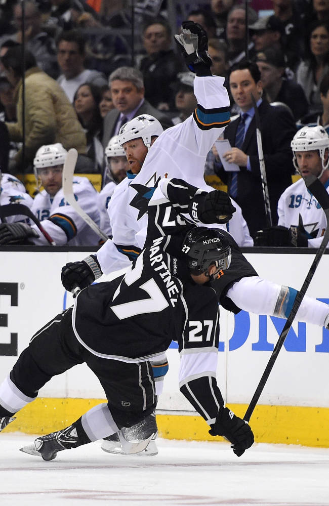 San Jose Sharks left wing Raffi Torres, top, collides with Los Angeles Kings defenseman Alec Martinez during the first period in Game 3 of an NHL hockey first-round playoff series , Tuesday, April 22, 2014, in Los Angeles