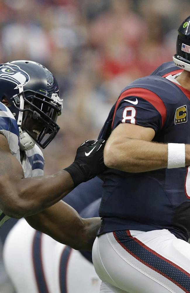 Seattle Seahawks' Chris Clemons, left, grabs Houston Texans' Matt Schaub (8) who looks to pass during the first quarter an NFL football game on Sunday, Sept. 29, 2013, in Houston