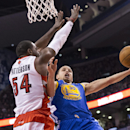 Golden State Warriors' Stephen Curry, right, scores on Toronto Raptors' Patrick Patterson during second half NBA basketball action in Toronto, Sunday, March 2, 2014 The Associated Press