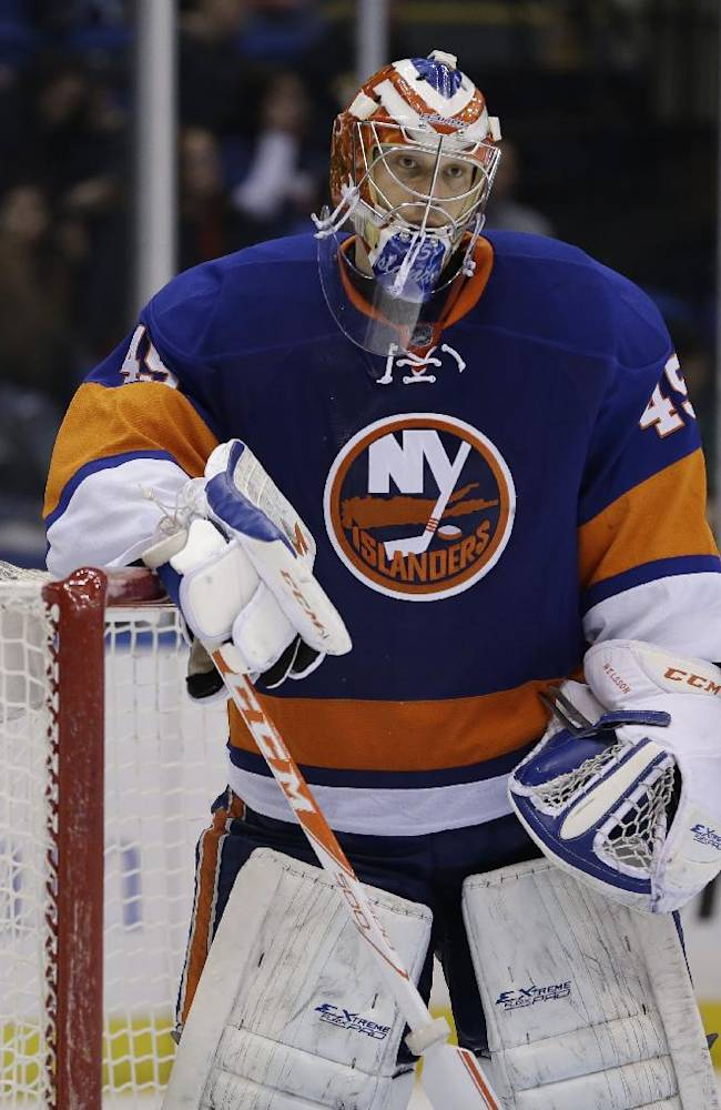 New York Islanders goalie Anders Nilsson passes after being scored on during the third period of the NHL hockey game against the Minnesota Wild, Tuesday, March 18, 2014, in Uniondale, N.Y. The Wild defeated the Islanders 6-0