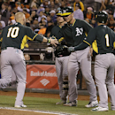 Oakland Athletics' Daric Barton (10) celebrates with teammates after scoring on Sam Fuld's three-run triple during the sixth inning of an exhibition baseball game against the San Francisco Giants in San Francisco, Friday, March 28, 2014 The Associated Pre