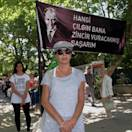 Turks stand in a silent protest in Kugulu Park in Ankara, Turkey, Wednesday, June 19, 2013. After weeks of sometimes-violent confrontation with police, Turkish protesters have found a new form of resistance: standing still and silent. The banner with an image of Turkey's founder Kemal Ataturk reads: