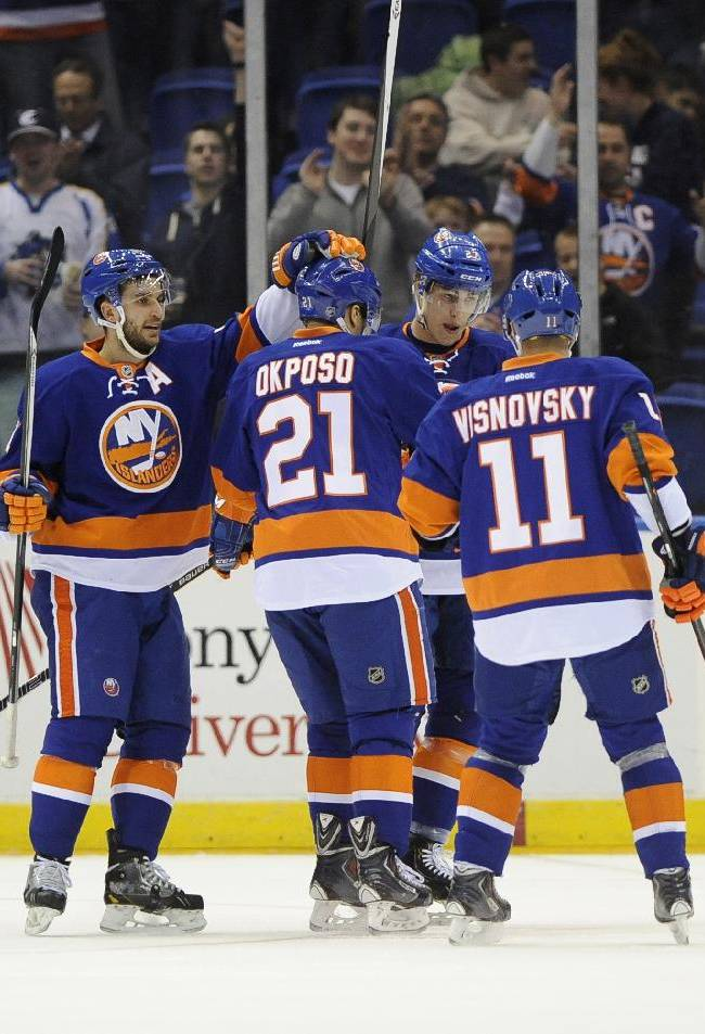 New York Islanders' Frans Nielsen (51), Anders Lee (27), and Lubomir Visnovsky (11) congratulate New York Islanders right wing Kyle Okposo (21) after Okposo scored against the Buffalo Sabres in the first period of an NHL hockey game on Saturday, March 15, 2014, in Uniondale, N.Y. Nielsen also scored in the first period