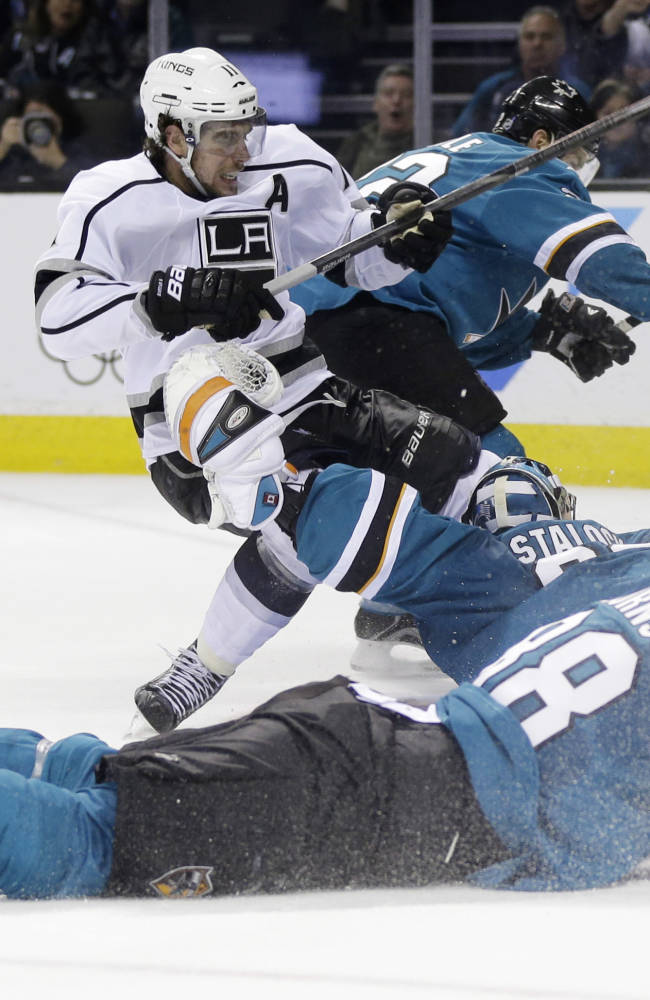 Los Angeles Kings' Anze Kopitar, of Slovenia, top left, trips over San Jose Sharks goalie Alex Stalock as he scores during the second period of an NHL hockey game on Monday, Jan. 27, 2014, in San Jose, Calif