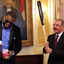 Boston Red Sox designated hitter David Ortiz, left, presents Dominican Republic President Danilo Medina with a ball and a bat during a meeting at the National Palace in Santo Domingo, Dominican Republic, Thursday, Nov. 28, 2013. Ortiz and fellow players o