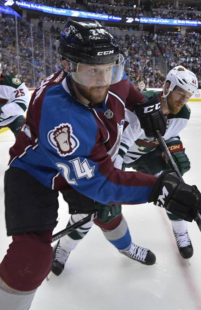 Colorado Avalanche right wing Marc-Andre Cliche (24) and Minnesota Wild center Kyle Brodziak (21) clear the puck from  the corner during the second period in Game 1 of an NHL hockey first-round playoff series on Thursday, April 17, 2014, in Denver