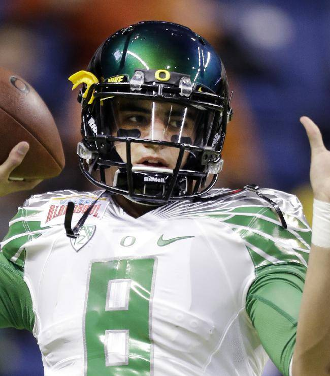 This Dec. 30, 2013, file photo shows Oregon's Marcus Mariota warms up for the Valero Alamo Bowl NCAA college football game against Texas in San Antonio. Mariota hears the jokes about his course load this semester: yoga and golf. For those who suggest he might want to add an elective in underwater basketweaving, the reality is this: The star quarterback for No. 3 Oregon finished his degree requirements in just three years
