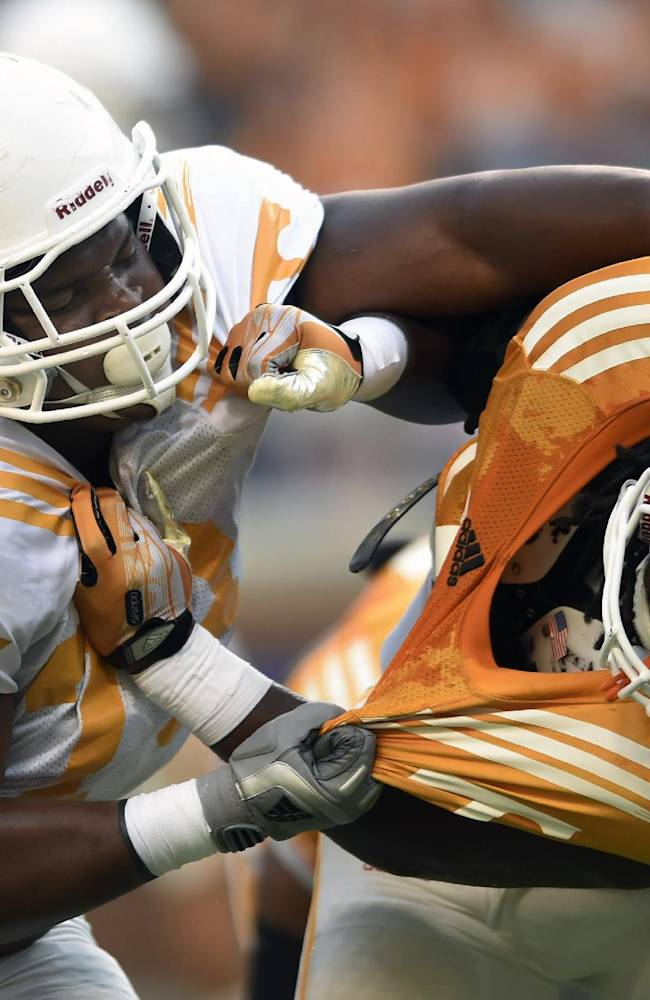Tennessee offensive lineman Jashon Robertson (73), left, overpowers Tennessee linebacker Jalen Reeves-Maybin (34), right, during Tennessee's open practice at Neyland Stadium in Knoxville on Saturday, Aug. 16, 2014