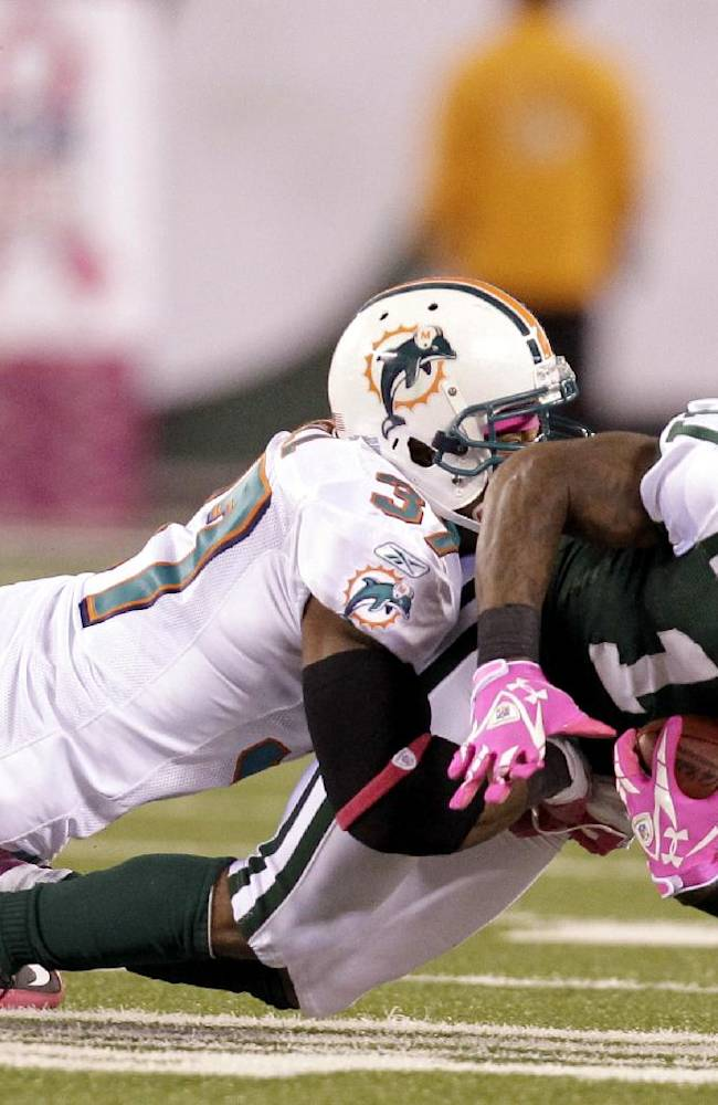 In this Oct. 17, 2011, file photo, New York Jets' Jeremy Kerley (11) is tackled by Miami Dolphins' Yeremiah Bell during the third quarter of an NFL football game in East Rutherford, N.J. Watching an NFL game two years ago saved a Staten Island woman's life. She wondered why the Dolphins and Jets were wearing all that pink. Moments after she was told it was for breast cancer awareness, she performed her first self-examination and discovered a lump. Two years later, she's cancer free