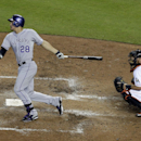 Colorado Rockies' Nolan Arenado follows through with an RBI-single to score Troy Tulowitzki as Miami Marlins catcher Jeff Mathis looks on during the fifth inning of a baseball game, Thursday, April 3, 2014, in Miami The Associated Press