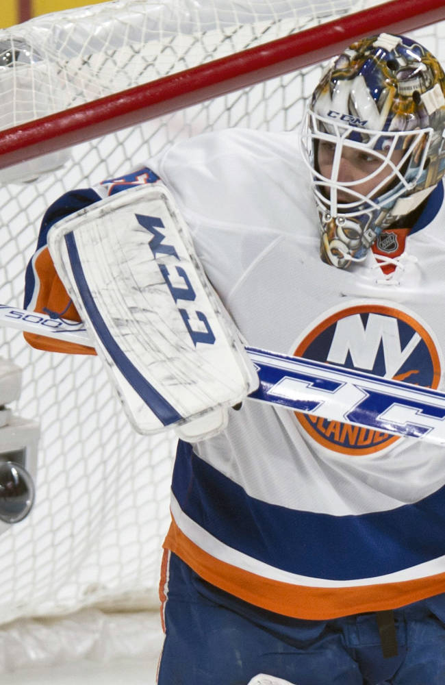New York Islanders goalie Kevin Poulin deflects a shot during first period of an NHL hockey game against the Montreal Canadiens on Sunday, Nov. 10, 2013, in Montreal