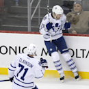 Toronto Maple Leafs left wing James van Riemsdyk, top, celebrates with teammate David Clarkson (71) after scoring a goal against the New Jersey Devils during the third period of an NHL hockey game, Wednesday, Jan. 28, 2015, in Newark, N.J. The Devils won