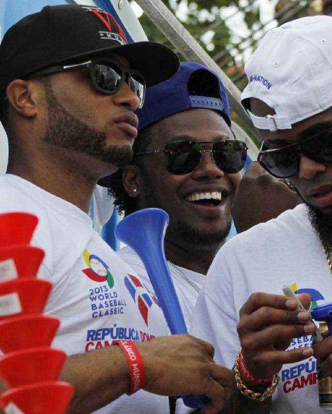 Dominican Republic baseball players, from left, Robinson Cano, Hanley Ramirez and Jose Reyes ride atop a truck during the 2013 World Baseball Classic victory celebration in Santo Domingo, Dominican Republic, Thursday, Nov. 28, 2013. The Dominican Republic team won the third edition of the World Baseball Classic in March, finishing unbeaten in eight games
