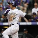 Colorado Rockies' Troy Tulowitzki, left, grounds out as San Francisco Giants catcher Buster Posey looks on to end the first inning of a baseball game in Denver, Saturday, May 18, 2013. (AP Photo/David Zalubowski)