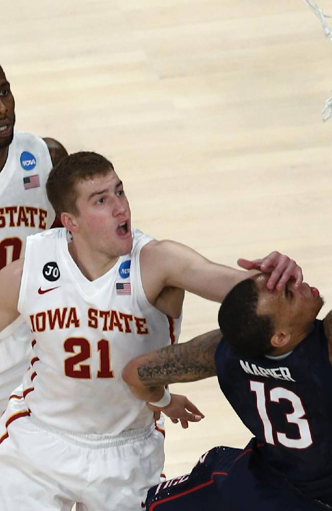 Connecticut's Shabazz Napier, right, is hit on the face by Iowa State's Matt Thomas while shooting during the second half in a regional semifinal of the NCAA men's college basketball tournament Friday, March 28, 2014, in New York. Iowa State's DeAndre Kane is at rear