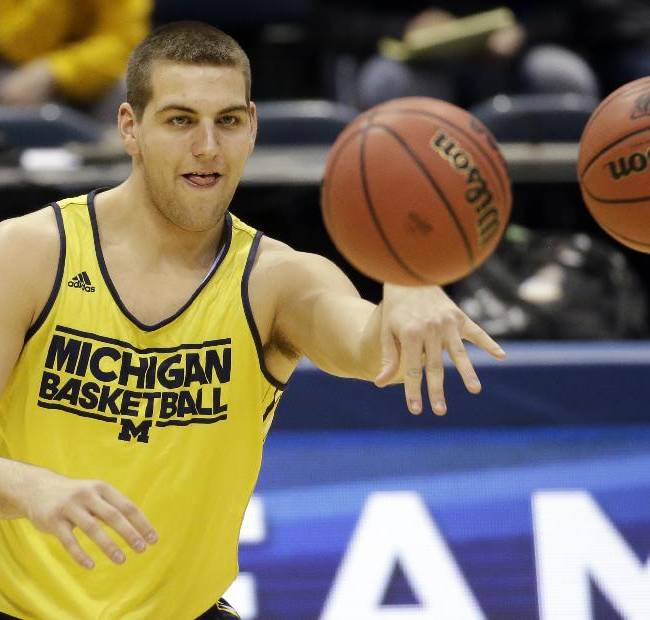 Michigan forward Mitch McGary passes the balls during a practice session for their NCAA college basketball tournament game Wednesday, March 19, 2014, in Milwaukee. Michigan plays Wofford on Thursday