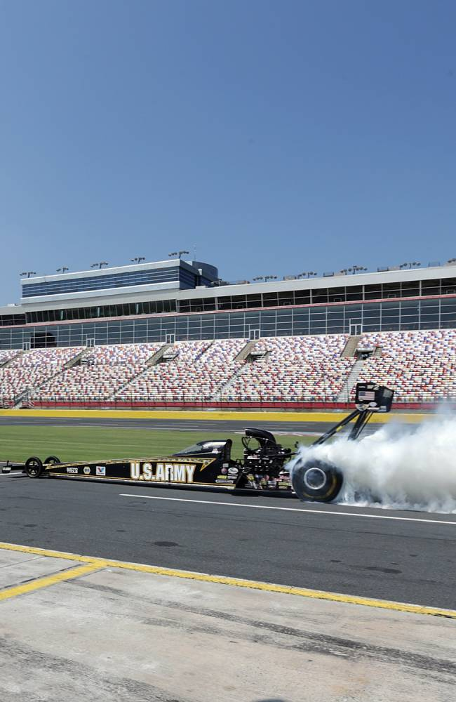 In this photo provided by Charlotte Motor Speedway, seven-time NHRA Top Fuel champion Tony Schumacher and five-time NASCAR Sprint Cup champion Jimmie Johnson perform a side-by-side burnout Wednesday, Sept. 11, 2013, on pit road at Charlotte Motor Speedway in Charlotte, N.C. NHRA's Countdown to the Championship opens this weekend at zMAX Dragway in Concord, while the NASCAR Chase for the Sprint Cup gets underway at Chicagoland Speedway. Charlotte Motor Speedway is the only facility that hosts playoff rounds for both major series