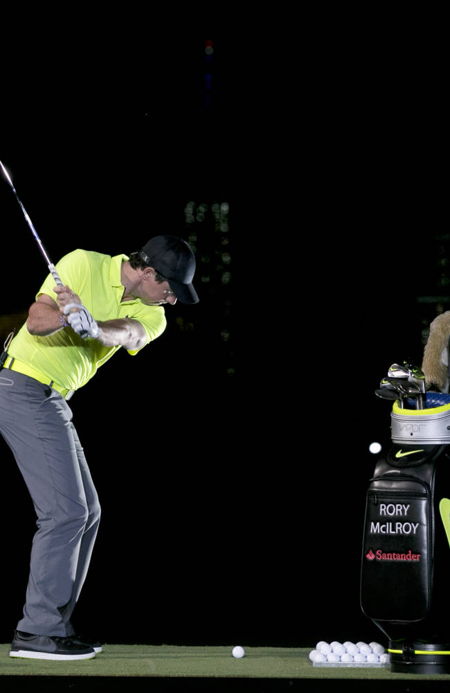 Golfer Rory McIlroy hits a ball into the darkness during a golfing demonstration, Monday, Aug. 18, 2014, in Jersey City, N.J